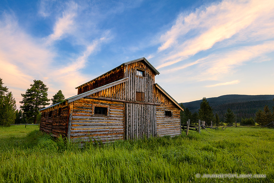 A beautiful wooden barn sits in the Kawuneeche Valley on the western side of Rocky Mountain National Park in Colorado.  Clouds lazily floated by as the sun set behind the Never Summer Range in the distance. - Colorado Photography
