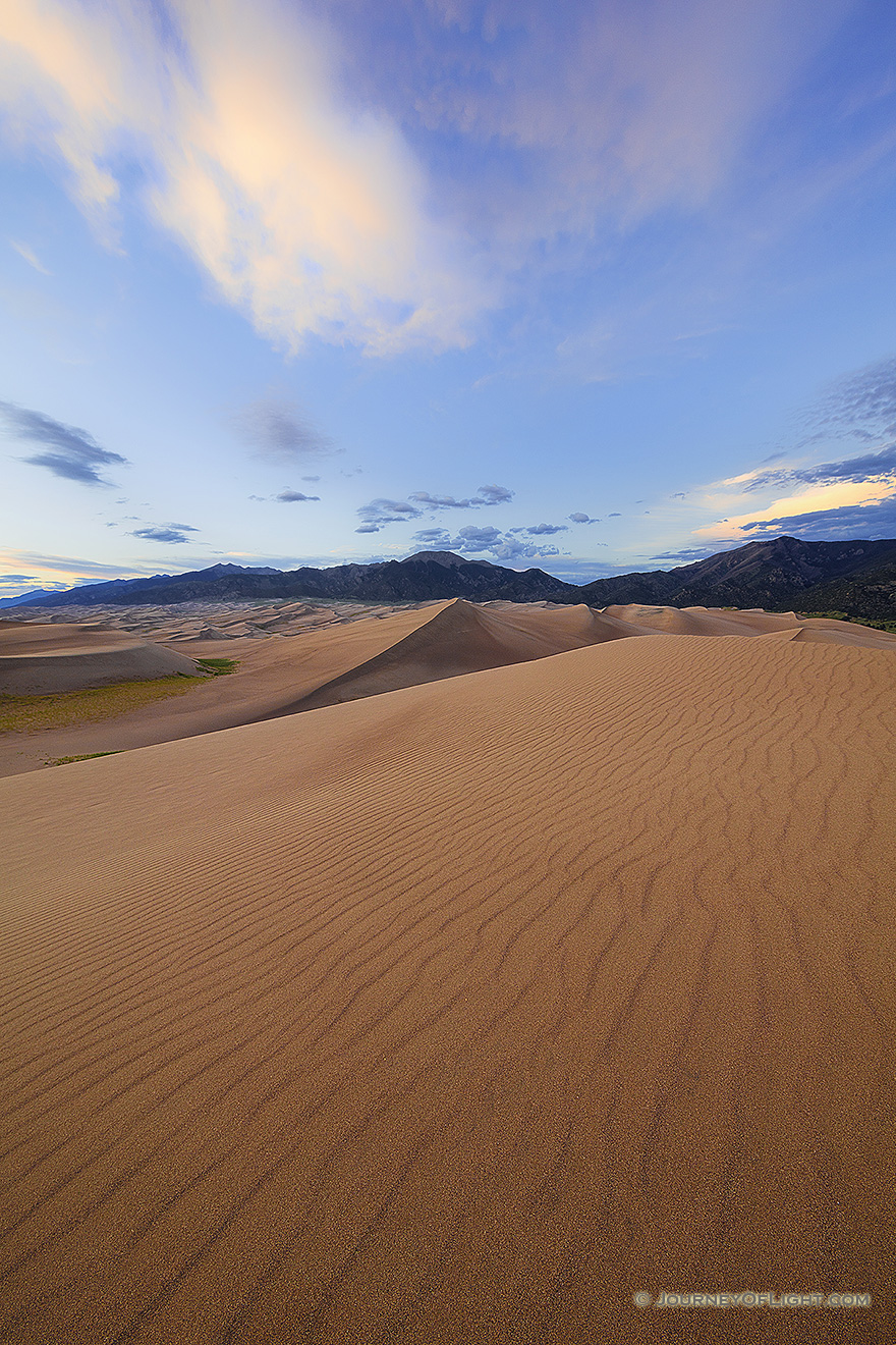 A rare combination of geologic forces combine to create these massive dunes, the largest in North America.  Rising in the distance is Mt. Herard, one of the tallest mountains of the San Juan range. - Great Sand Dunes NP Picture