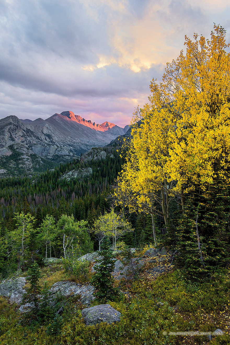 After a brief rainfall, on a cool autumn evening the last  bit of sun illuminates the peak of Long's Peak in Rocky Mountain National Park. - Colorado Picture