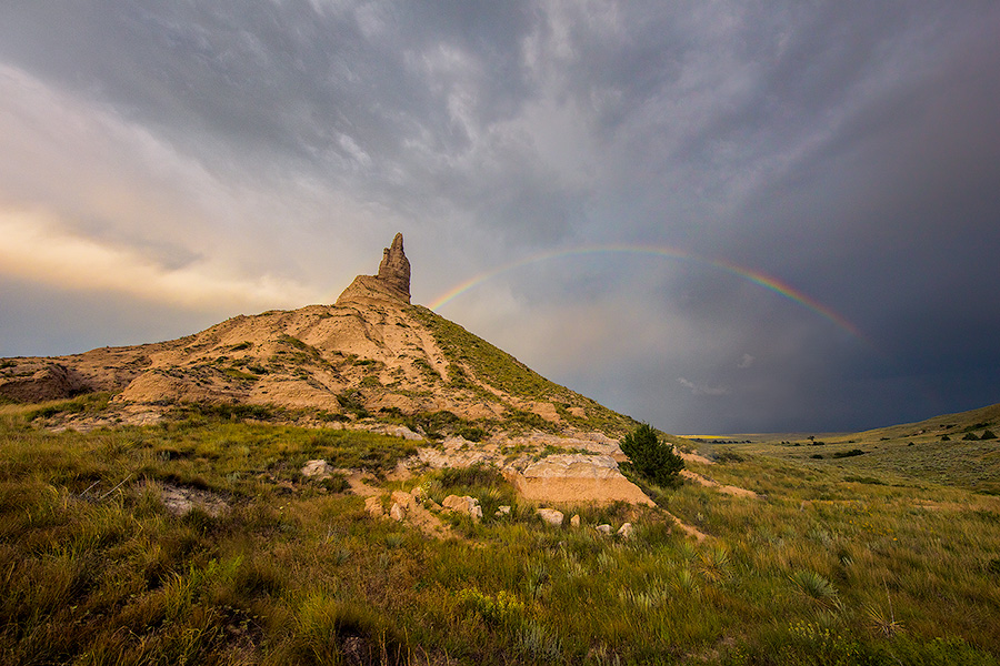 A scenic landscape Nebraska photograph of a rainbow over Chimney Rock in western Nebraska. - Nebraska Photography