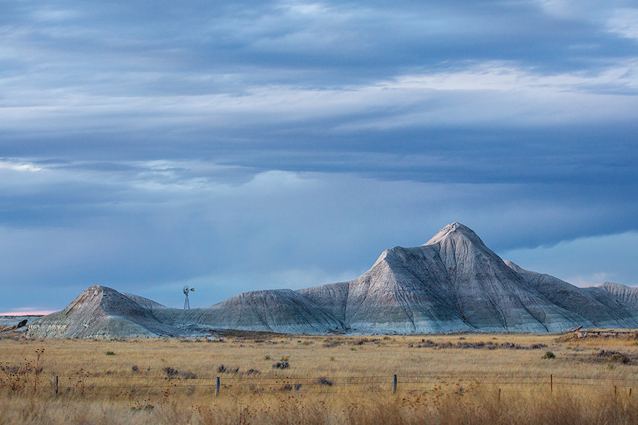 Scenic landscape photograph of a windmill and badlands during dusk in western Nebraska. - Nebraska Photography