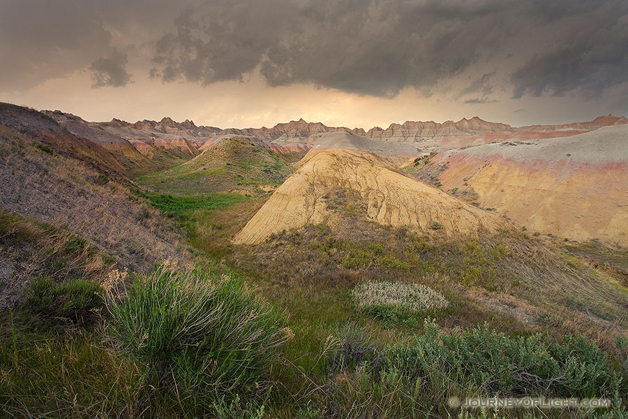 As a storm passes over Badlands National Park in South Dakota, the last light of the day illuminates a few distant clouds. - South Dakota Photography