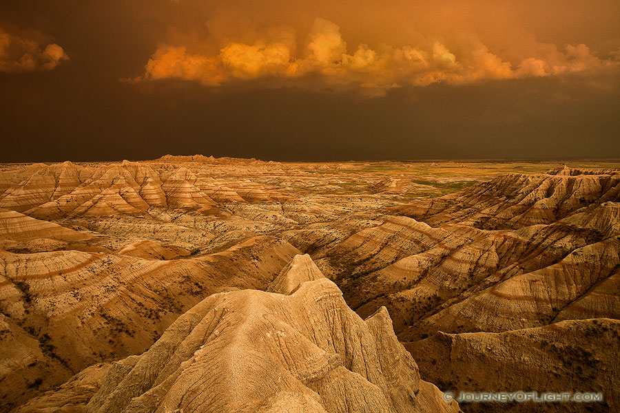 Facing east, the sky was nearly pitch black shrouded by the fierce storm that had just passed through.  As the sun dipped below the horizon the last rays hit the trailing storm clouds and the ambient warm light lit up the valley across the Badlands in South Dakota. - South Dakota Photography