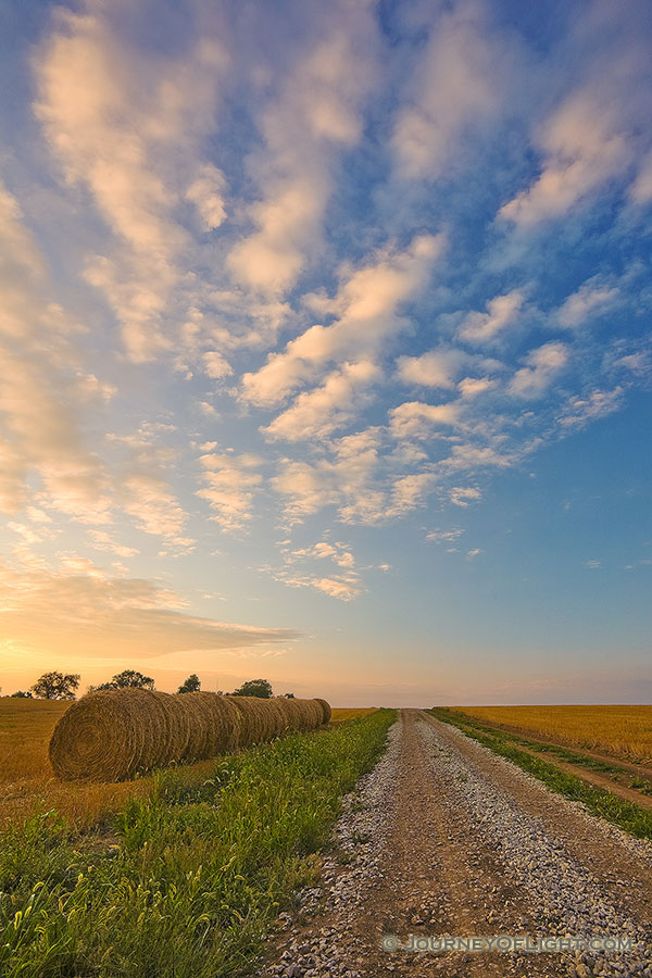 Hay bales line a country road that goes into the sunset while clouds float above. - Nebraska Photography