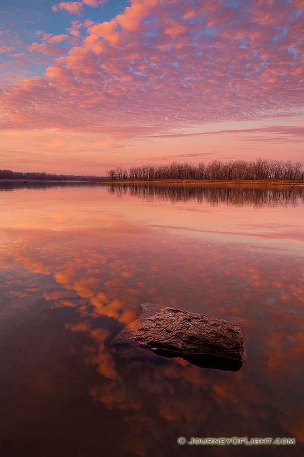 With nary a breeze and no other soul in sight, I enjoyed the vibrant colors brought forth from this sunrise in a quiet peacefulness and solitude. - Nebraska Photography