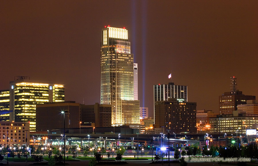 On September 11, 2006 Omaha, Nebraska paid tribute to the victims of 9/11 by hanging 2 large United States flags on the Woodmen tower and by shining two large lights into the sky. - Omaha Photography