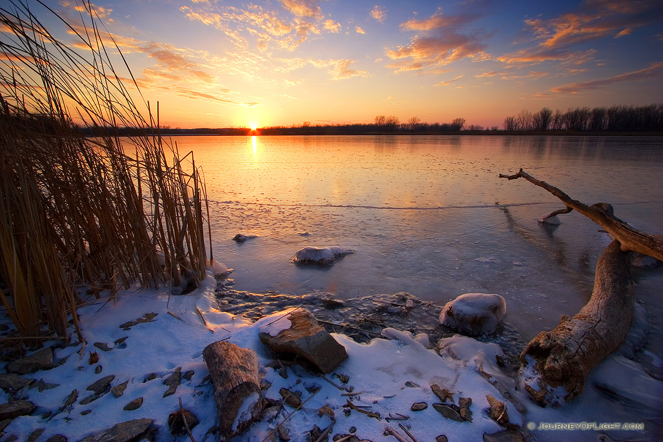 The sun reflects off a frozen lake in DeSoto National Wildlife Refuge in eastern Nebraska. - DeSoto Picture