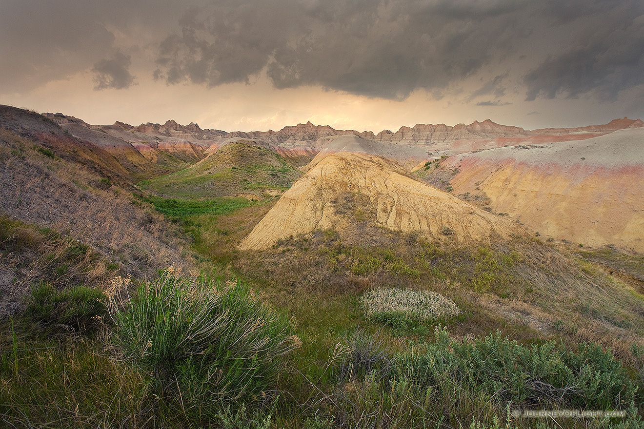 As a storm passes over Badlands National Park in South Dakota, the last light of the day illuminates a few distant clouds. - South Dakota Picture