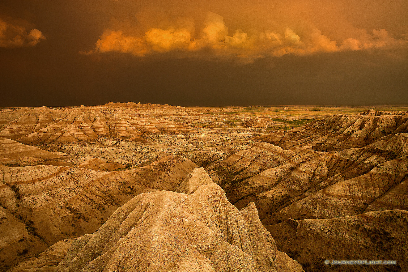 Facing east, the sky was nearly pitch black shrouded by the fierce storm that had just passed through.  As the sun dipped below the horizon the last rays hit the trailing storm clouds and the ambient warm light lit up the valley across the Badlands in South Dakota. - South Dakota Picture