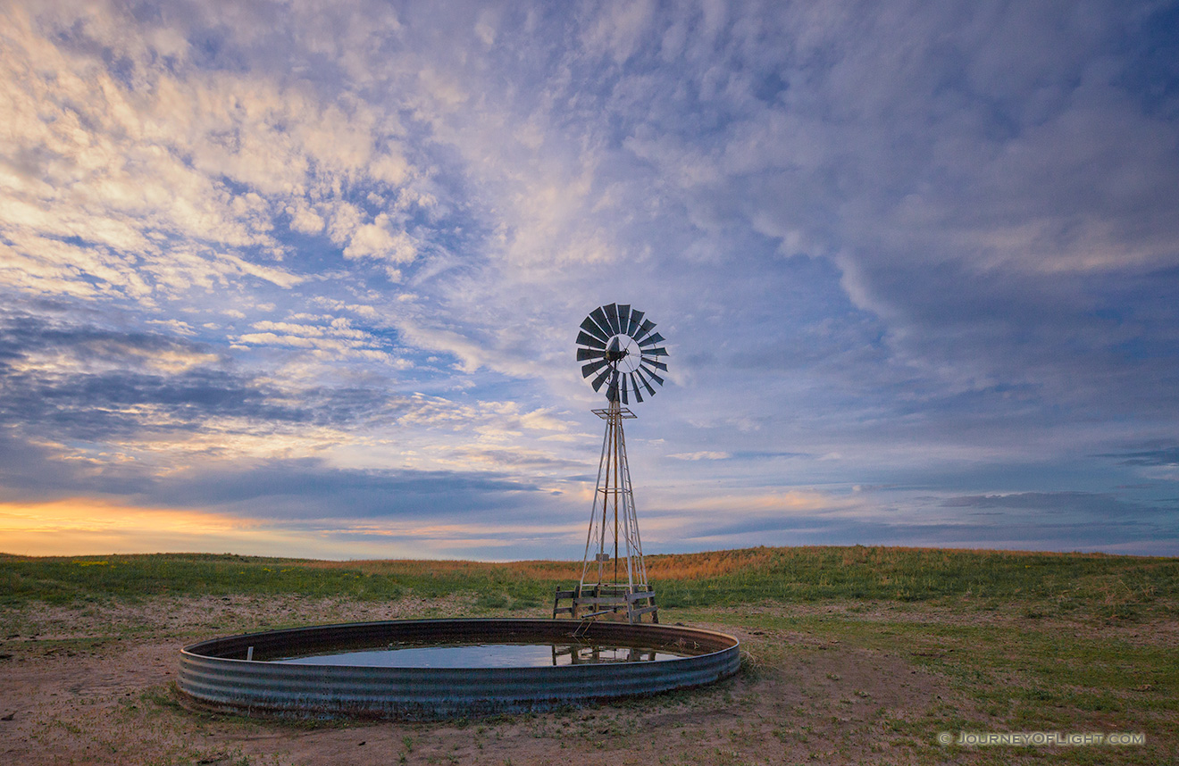 Dusk falls as clouds hover over a remote windmill in McKelvie National Forest in western Nebraska. - Sandhills Picture