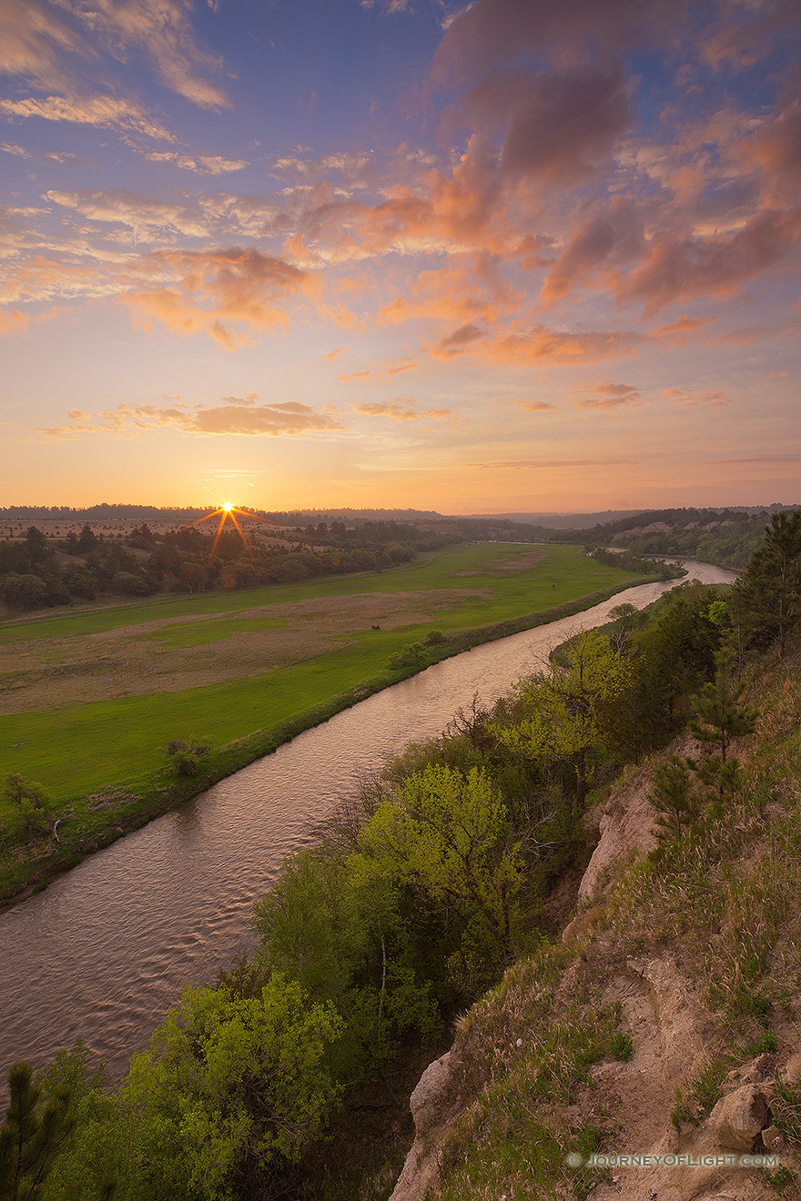The Niobrara is one of the most popular rivers for canoeing and tubing in the United States.  On a beautiful spring sunrise, the river lazily meanders into the east as the sun rises in the distance. - Valentine Picture