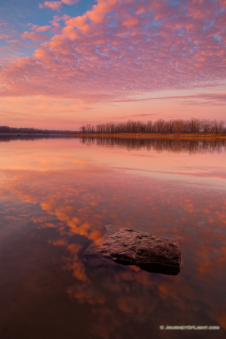 With nary a breeze and no other soul in sight, I enjoyed the vibrant colors brought forth from this sunrise in a quiet peacefulness and solitude. - Nebraska Picture