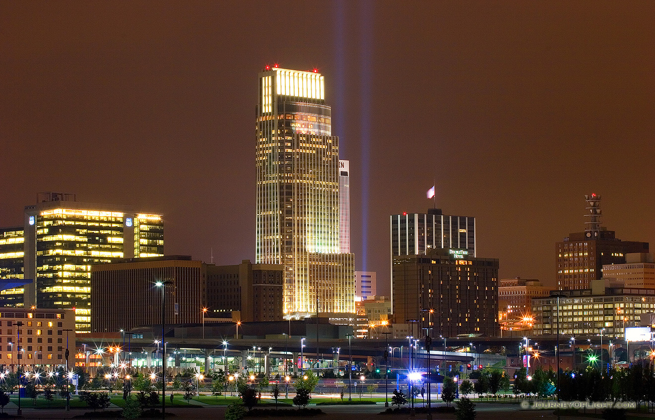 On September 11, 2006 Omaha, Nebraska paid tribute to the victims of 9/11 by hanging 2 large United States flags on the Woodmen tower and by shining two large lights into the sky. - Omaha Picture