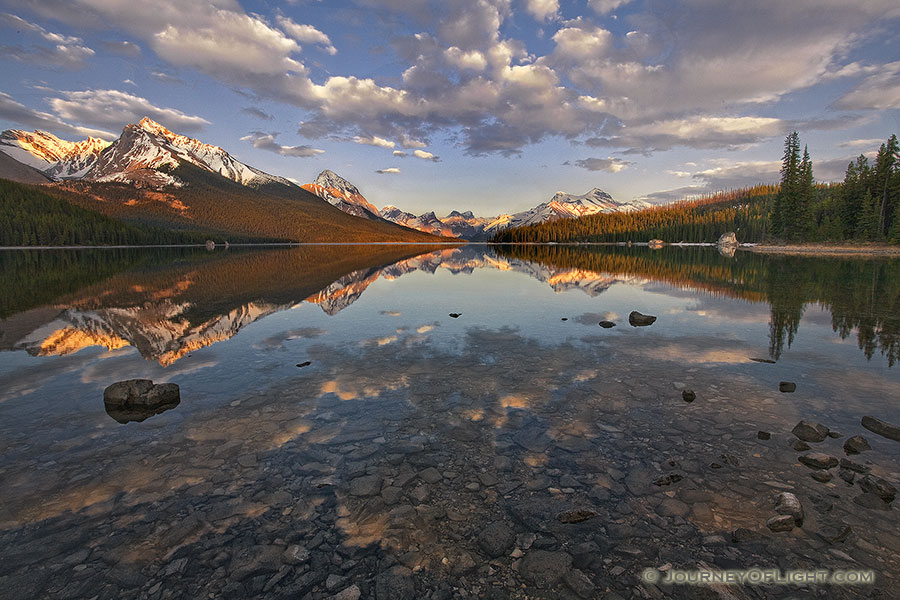 Clouds float lazily down the water as the last light hits at Maligne Lake located in Jasper National Park. - Canada Photography