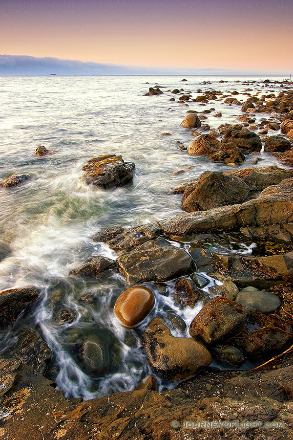 Close to the northwestern most tip of the continential United States, the waves of the Strait of the Juan de la Fuca lap against the rocks. - Pacific Northwest Photography