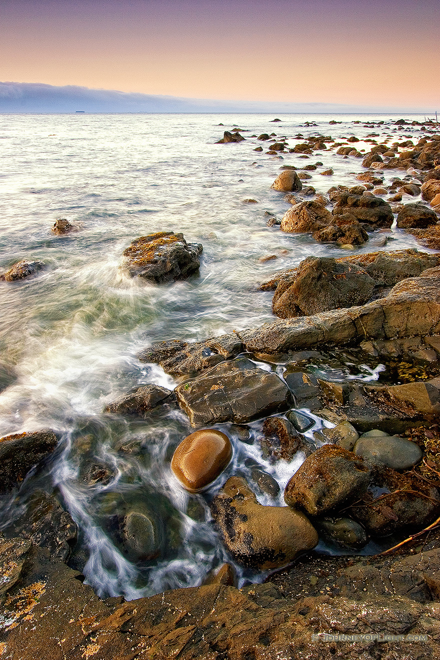Close to the northwestern most tip of the continential United States, the waves of the Strait of the Juan de la Fuca lap against the rocks. - Pacific Northwest Picture